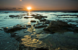 Sunset. Peaceful rocky shore during sunset Stock Images