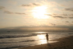 Sunset. Man standing along the shoreline at sunset Stock Photo