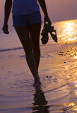 Sunset 2. Girl walking along the coastline in sunset 2 Royalty Free Stock Photography