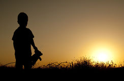 Sunset. Silhouette of a boy on a sunset background Stock Image