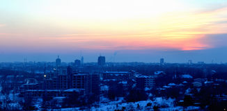 Sunset. Amazing winter sunset over busy city covered in snow with a beautiful mix of orange blue and white Royalty Free Stock Image