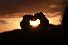 Sunset. Heart shape made with hands Stock Image