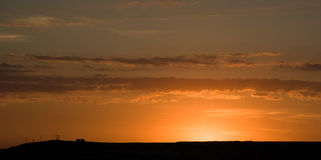 Sunset. A view of a golden sunset over a long, flat landscape Royalty Free Stock Images