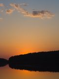 Sunset. Quiet lake over blue-orange sky Stock Photos