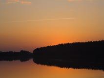 Sunset. Quiet lake over blue-orange sky Royalty Free Stock Photo