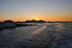 Sunset. Sun setting over fort lauderdale cruise terminal from a moving cruise ship heading out to sea Royalty Free Stock Photography