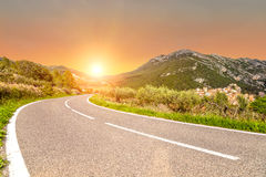 Sunset. In mountains and the road Stock Photography