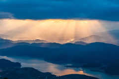 Sunset. Sun rays pass through the clouds over the mountains Royalty Free Stock Image