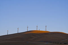 Sunset. Windfarm turbines on yellow grassed hills with blue cloudless skys Royalty Free Stock Image