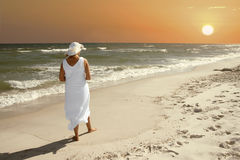 Sunset. A woman alone watching the sunset on the beach royalty free stock photo