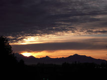 Sunset. Bright colors of clouds and sun at sunset over the mountains Stock Photo