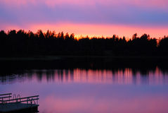 Sunset. Over a Lake and Pier in Finland, Scandinavia, turning clouds in purple and orange colors royalty free stock image
