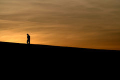 Into the Sunset. A distraught boy walks off toward the sun Stock Photo