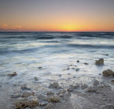 Sunset. Florida sunset on a rocky beach. Slow shutter for creamy, smooth waves royalty free stock photos