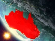 Sunset above Australia on Earth. Australia during sunset highlighted in red on planet Earth with clouds. 3D illustration. Elements of this image furnished by Stock Images