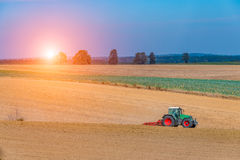 Sunset above autumn field works Royalty Free Stock Photography