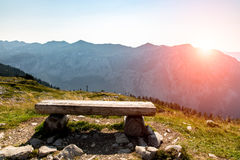 Sunset above the bench at the shore of the lake Stock Image