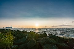 The polder dike with stone bollards along the Ijsselmeer at Flev. Sunset above a binary lake in the Netherlands with views over the water and the setting sun Royalty Free Stock Images