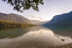 Sunset above the Bohinj lake, Slovenia. Magical evening color of sun with reflection in water. Julian Alps in background. Triglav. National park royalty free stock photography