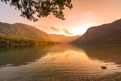 Sunset above the Bohinj lake, Slovenia. Magical evening color of sun with reflection in water. Julian Alps in background. Triglav. National park royalty free stock image