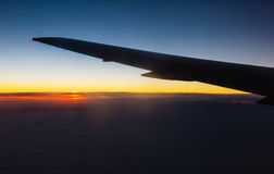 Sunset above the clouds b flying a plane Royalty Free Stock Image