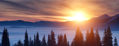 Sunset in the winter mountains. Sunset above the clouds in the mountains in winter Royalty Free Stock Images
