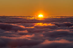 Sunset above the clouds. Spectacular view of a sunset above the clouds from the top of the mountain Stock Image