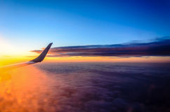 Sunset above the clouds. The view from the airplane at the clouds during sunset Stock Photos