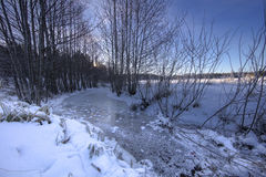 Sunset above a frozen stream, in a winter landscape. Royalty Free Stock Images