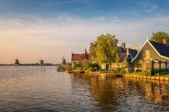 Sunset above farm houses and windmills of Zaanse Schans in Holland Royalty Free Stock Images