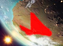 Sunset above Mali on Earth. Mali during sunset highlighted in red on planet Earth with clouds. 3D illustration. Elements of this image furnished by NASA Stock Image