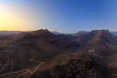 Sunset above mountains and canyon. With rural road on bottom Royalty Free Stock Photos