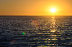 Sunset above the ocean with lens flares Stock Photos