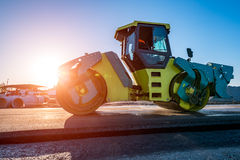 Sunset above the road roller working on the construction site Royalty Free Stock Photography