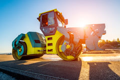 Sunset above the road roller working on the construction site Stock Photo