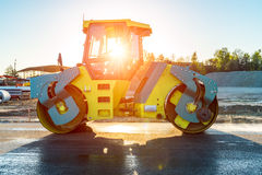 Sunset above the road roller working on the construction site Royalty Free Stock Photos