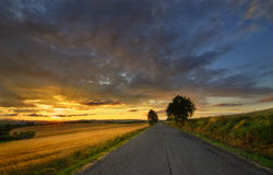 Sunset above the road. Summer evening with sunset in countryside Stock Images