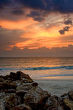 Sunset above a rocky beach. Craggy rocks and boulders on the beach lead the viewers eye into this beautiful sunset image of  florida's naples beach in the gulf Royalty Free Stock Image