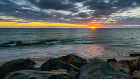 Sunset above the sea on a rocky beach Royalty Free Stock Photo