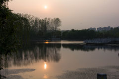 Sunset. Above a small lake which reflects the setting sun Stock Images