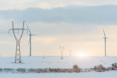 Sunset above windmill and powerlines on the field in winter Stock Images