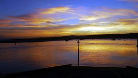 Sunset across The River Exe Estuary in Exmouth Uk. Golden sunrays of a sunset across the water in Exmouth a popular holiday town in Devon South West England royalty free stock image