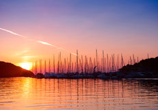 Sunset in Adriatic sea bay. Yacht silhouettes and calm water in sunset light Stock Photo