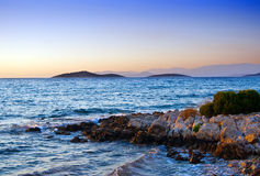 Sunset At Aegean Sea. Beautiful evening view of the mountains and coast with rocks at Aegean Sea Stock Images