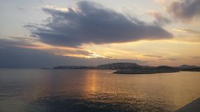 Sunset at Aegean sea. Cloudy sunset at Aegean sea from the port of Piraeus in Greece royalty free stock photos