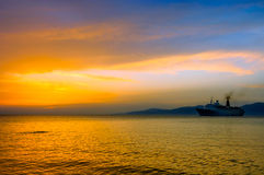 Sunset on Aegean sea with cruise ship silhouette Royalty Free Stock Photography