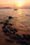 Sunset at Aegean sea, Greece. Sunset at sea with a boat and stones at foreground, Greece, Halkidiki, near Ouranoupoli Stock Image