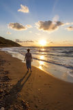 Sunset on the Aegean Sea. Women walking on Pebble beach on the Aegean Sea at sunset Royalty Free Stock Images