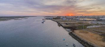 Sunset aerial panoramic seascape view of Olhao dockyard, waterfront to Ria Formosa natural park. And Armona island. Algarve. Portugal Stock Photo