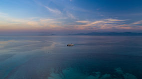 Sunset aerial view of clear blue sea with ferry boat Royalty Free Stock Image